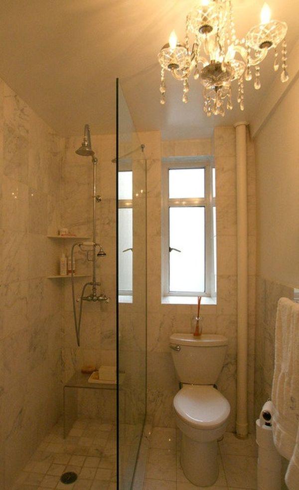 Banheiro pequeno com lustre e divisória de vidro